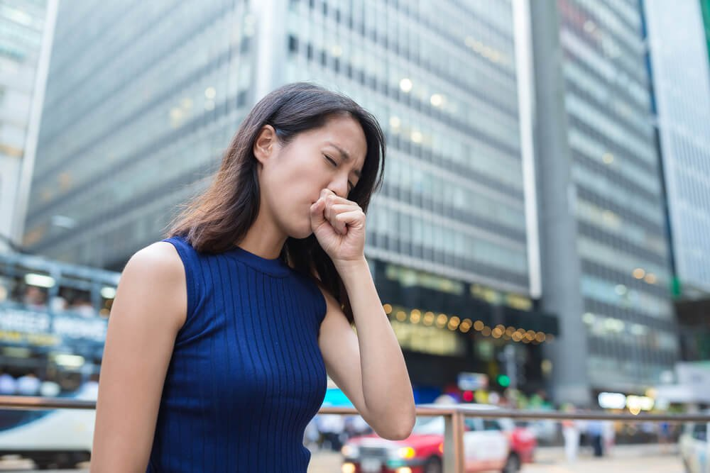 woman coughing in the city